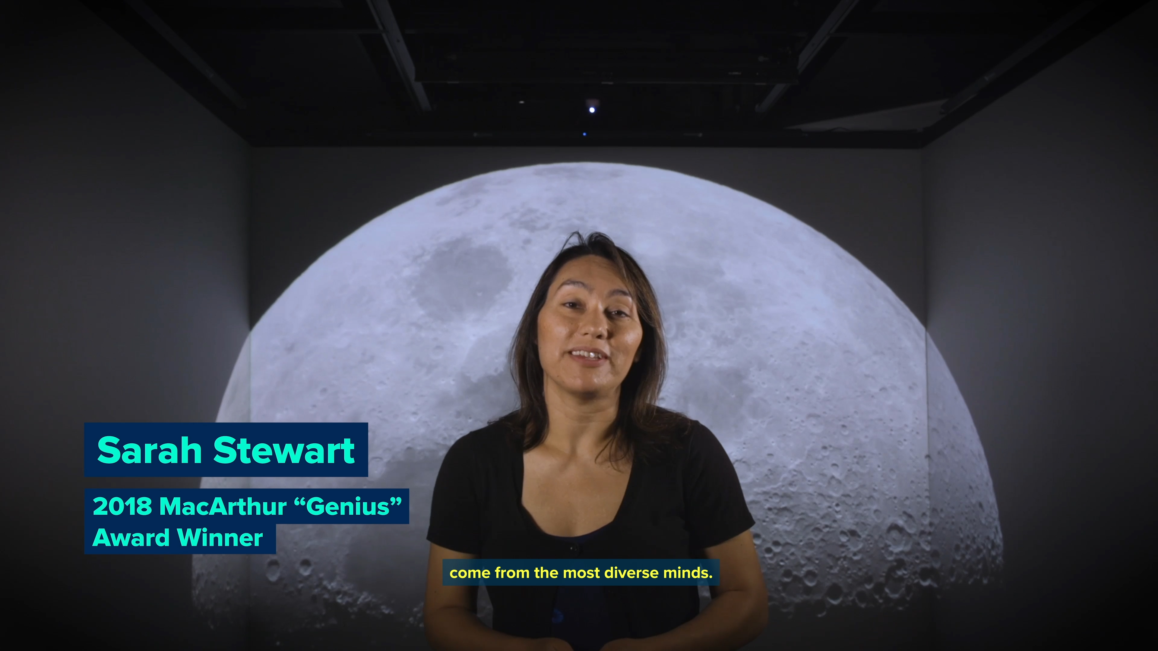 Lower thirds text over interview of woman in room with background photo of the moon