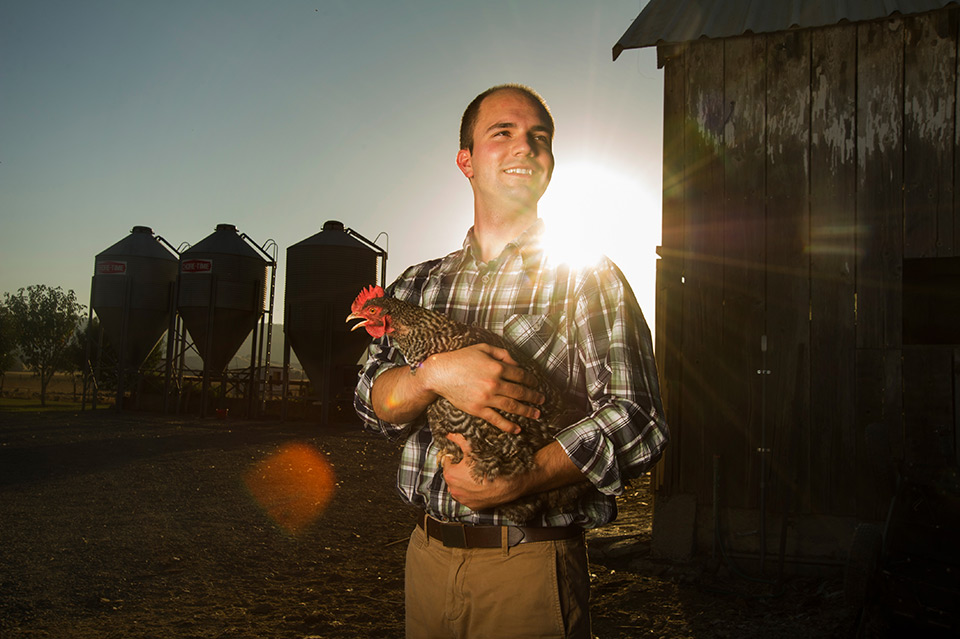 Award-winning photo of Edward Silva standing in front of a chicken coop while holding a hen.