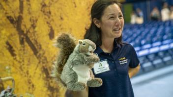 A staff member from the Arboretum holds a squirrel puppet