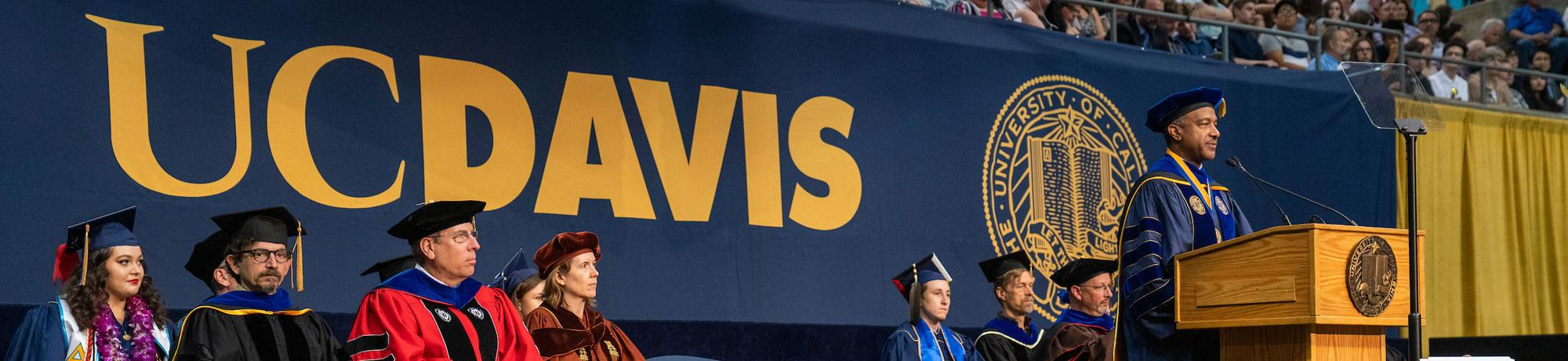 Gary May speaking at Commencement with a large UC Davis logo in the background