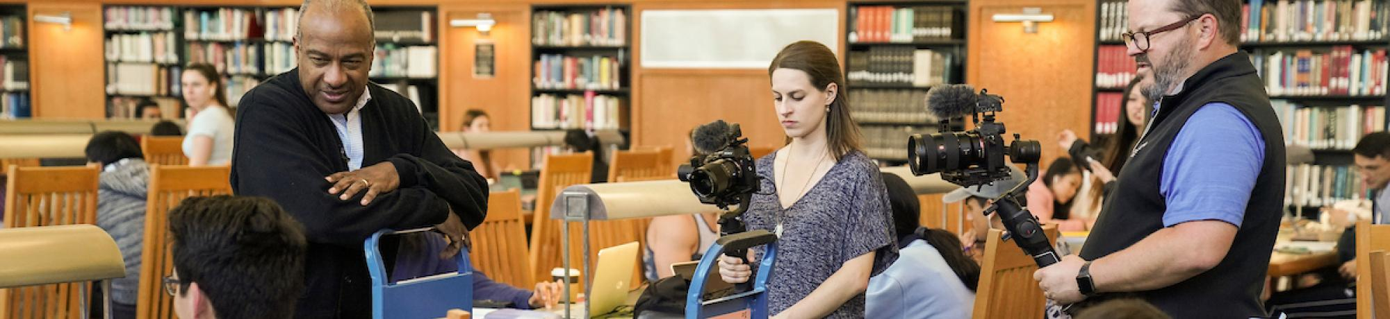 Two video producers filming a conversation in a library